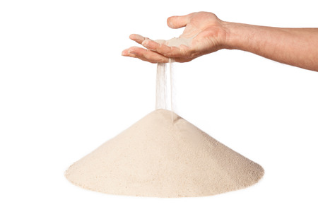 sand grains: sand running through hand as a symbol for time running out.Isolated on a white background