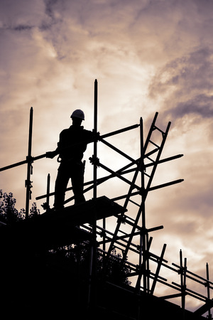 buildingsite: silhouette of construction worker with ladder on scaffolding. Purple toned