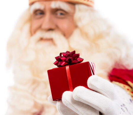 nicolaas: friendly Santa Claus with small gift  .Selective focus on hand with gift