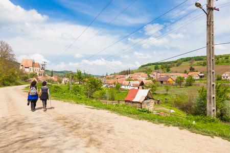 two female hikers walking on village road near Biertan in Transylvania Romania photo