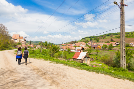 biertan: two female hikers walking on village road near Biertan in Transylvania Romania Stock Photo