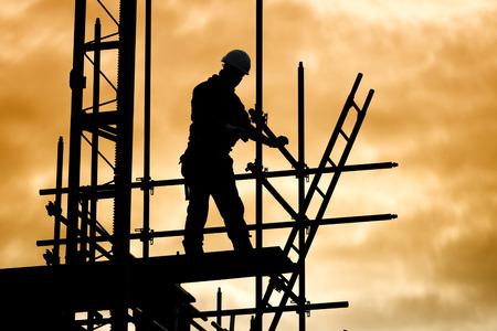 silhouette de travailleur de la construction contre le ciel sur un échafaudage avec échelle sur chantier au coucher du soleil Banque d'images
