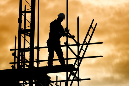 silhouette of construction worker against sky on scaffolding with ladder on building site at sunset