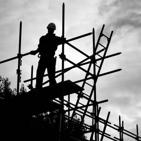ladder: silhouette of construction worker against sky on scaffolding with ladder on building site.Monochrome