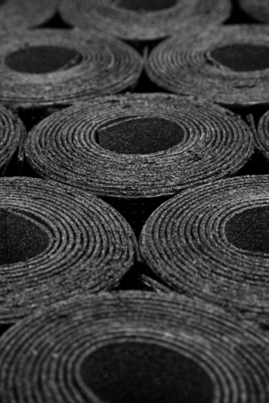 Rolls of new black roof coating or bitumen. Focus on centre Foto de archivo