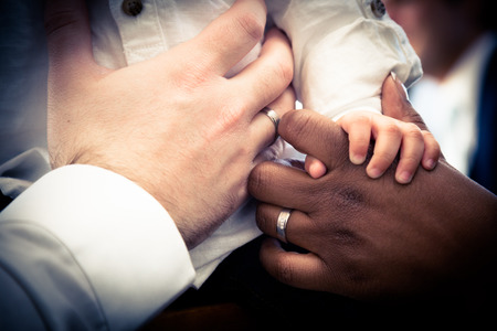 Close-up of hands Interracial couple holding their child. Vintage look with vignette. Focus on the center Stockfoto