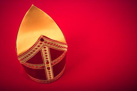 Mitre of mijter van Sinterklaas. Op rode achtergrond met kopie ruimte en vignet. Een deel van een Nederlandse traditie Sancta Stockfoto