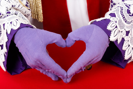 nicolaas: close up of hands of Sinterklaas with purple gloves and ring