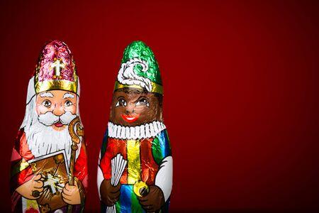 sinterklaas: Close up of Sinterklaas and Black Pete . Saint  Nicholas chocolate figure of  Dutch character of Santa Claus on red background. Stock Photo