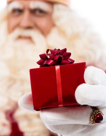 zwarte: friendly Santa Claus with small gift  .Selective focus on hand with gift