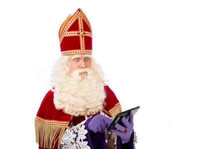 nicolaas: Sinterklaas looking on tablet. isolated on white background. Dutch character of Santa Claus