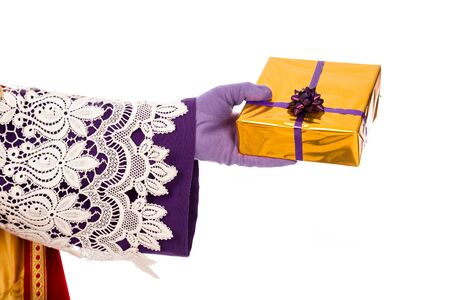 Hand of sinterklaas  with gift . typical Dutch character part of a traditional event celebrating the birthday of Sinterklaas (Santa Claus) in december. 스톡 콘텐츠