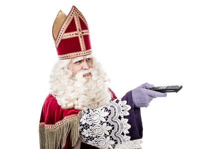nicolaas: St. Nicholas with TV remote .Old fashioned vintage look isolated on white background. Dutch character of St. Nicholas