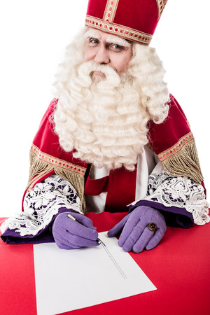 nicolaas: Sinterklaas writing on a checklist. Isolated on white background. Vintage editing Stock Photo