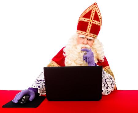 Sinterklaas avec un ordinateur portable. isolé sur fond blanc. Néerlandais caractère du Père Noël