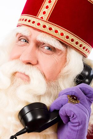 nicolaas: Sinterklaas with old  telephone.Vintage look. isolated on white background. Dutch character of Santa Claus