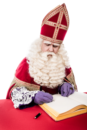 Sinterklaas met boek. geïsoleerd op een witte achtergrond. Nederlandse karakter van de Kerstman photo