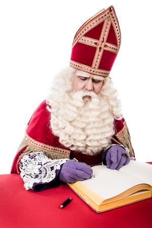 sinterklaas: Sinterklaas with book . isolated on white background. Dutch character of Santa Claus