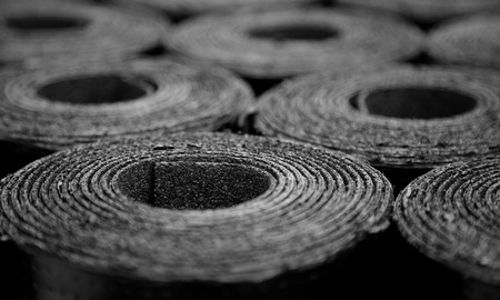 ruberoid: Closeup of Rolls of new black roofing felt or bitumen. Selective focus