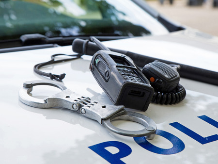 police equipment: Police equipment on a  police car.  Handcuffs, baton and pager on top of a police car. Selective focus Stock Photo