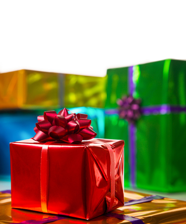 nicolaas: colorful gift boxes with a white background. Focus on red bow. Stock Photo