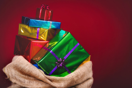 Sack of Sinterklaas with gifts .Burlap bag on red background. Vintage editing. Stockfoto