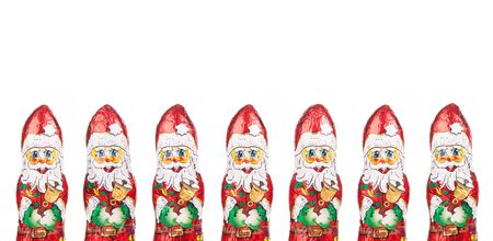 Close-up of Santa Claus chocolate figures in a row. xmas Border Isolated on white background