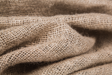 burlap or jute open woven texture background. Shallow DOF