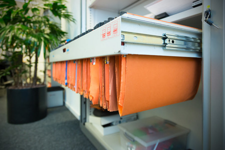 old and used orange paper File Folders in a metal filing cabinet.Cupboard with suspension files