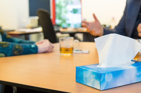 conversation between manager and sad employee. Focus on tissues