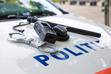 Police equipment on a dutch police car.  Handcuffs, baton and phone on top of a police car. Selective focus