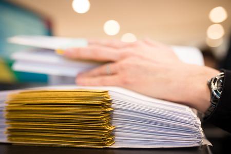 Close-up van vrouwelijke hand met dossiers op het kantoor. Werken aan een stapel bestanden. Ondiepe DOF Stockfoto