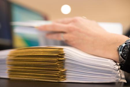 Close-up van vrouwelijke hand met dossiers op het kantoor. Werken aan een stapel bestanden. Stockfoto
