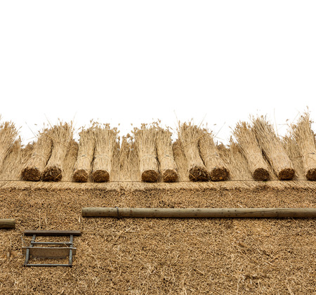 Thatched  roof of a house, border of  straw. Isolated on a white background