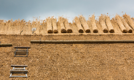 Thatcher thatching a roof of a house with new straw.Thatched roof of a home with tools Stockfoto