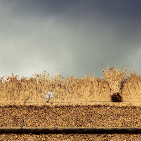 Thatcher tools  on thatched  roof of a house with new straw.Thatched roof of a home Stockfoto