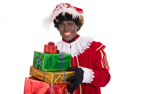Happy Zwarte Piet or Black Pete holding gifts.  Stockfoto
