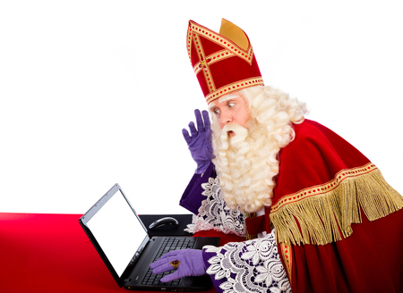 Sinterklaas looking on notebook. isolated on white background. Dutch character of Santa Claus