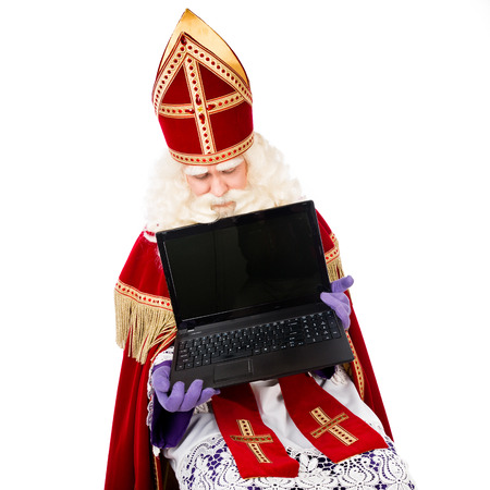 Sinterklaas is looking down on laptop or notebook. isolated on white background. Dutch character of Santa Claus