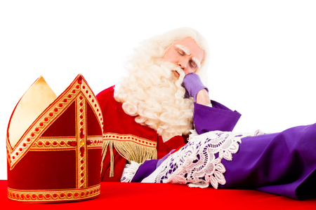 Saint  Nicholaswith mitre on table is tired and asleep. Isolated on white background