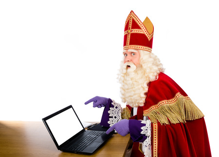 Sinterklaas pointing on laptop. isolated on white background. Dutch character of Santa Claus or saint nicholas Stockfoto