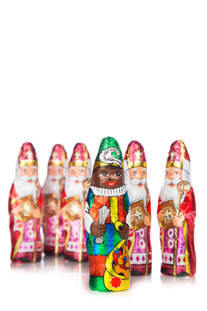 Sinterklaas and black pete. Saint Nicholas chocolate figures of Dutch character of Santa Claus. On a red background.