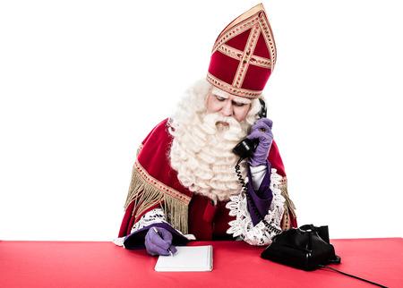 Sinterklaas met oude telefoon Vintage look geïsoleerd op witte achtergrond Nederlandse karakter van de kerstman Stockfoto