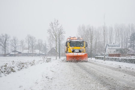 Snowplow removes snow off icy road in winter Stock Photo - 110453825