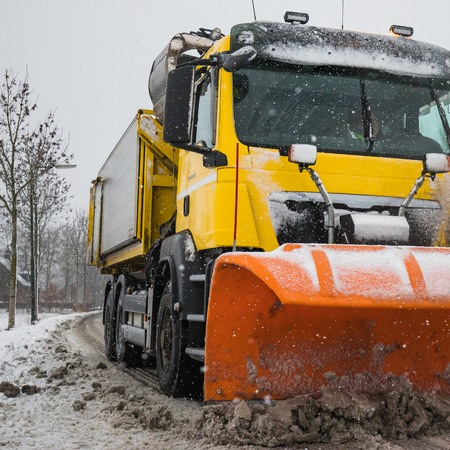 Snowplow removes snow off icy road in winter