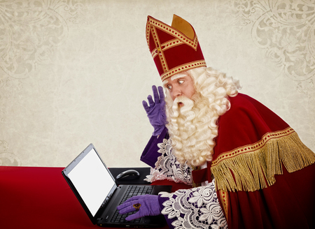 Sinterklaas looking on notebook. Vintage look. Dutch character of Santa Claus Stockfoto
