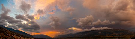 dramatic panorama sky with thunderclouds and mountains at sunset
