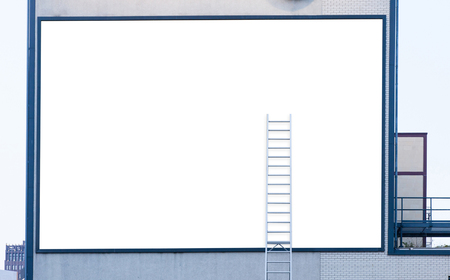 Large Empty white billboard with ladder on industrial building Stockfoto