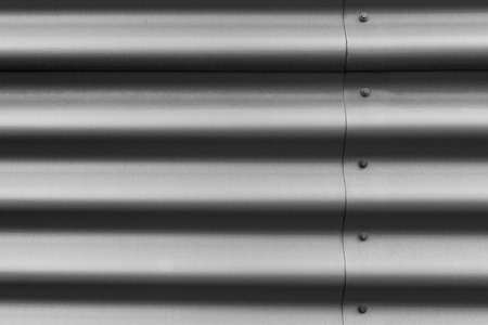 Detail of silver corrugated metal with bolts Stockfoto