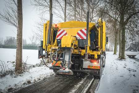 Winter service truck spreading salt and sand on the road surface to prevent icing Stockfoto